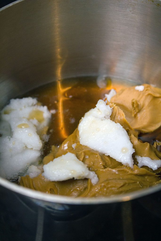 Peanut butter, coconut oil, and maple syrup being combined in saucepan