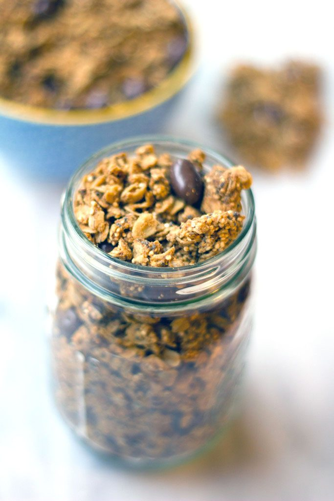 Overhead view of a mason jar filled with peanut butter granola with quinoa, chia seeds, and chocolate-covered raisins with bowl of granola in background