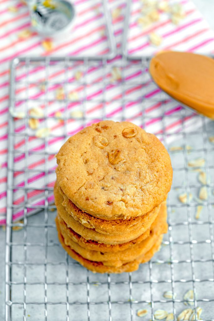 Bird's eye view of peanut butter sandwich cookies stacked on top of each other on cooling rack with spoon full of peanut butter and oats scattered everywhere