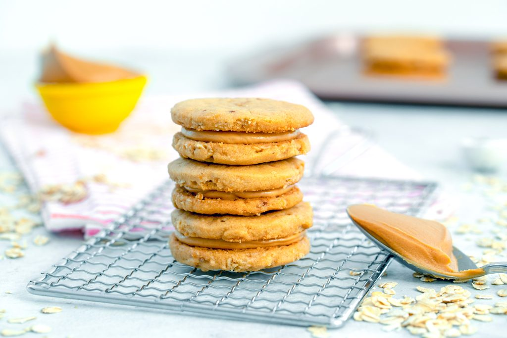 Landscape head-on view of three peanut butter sandwich cookies on a cooling rack with spoonful of peanut butter, cut of peanut butter, more cookies, and oats in background