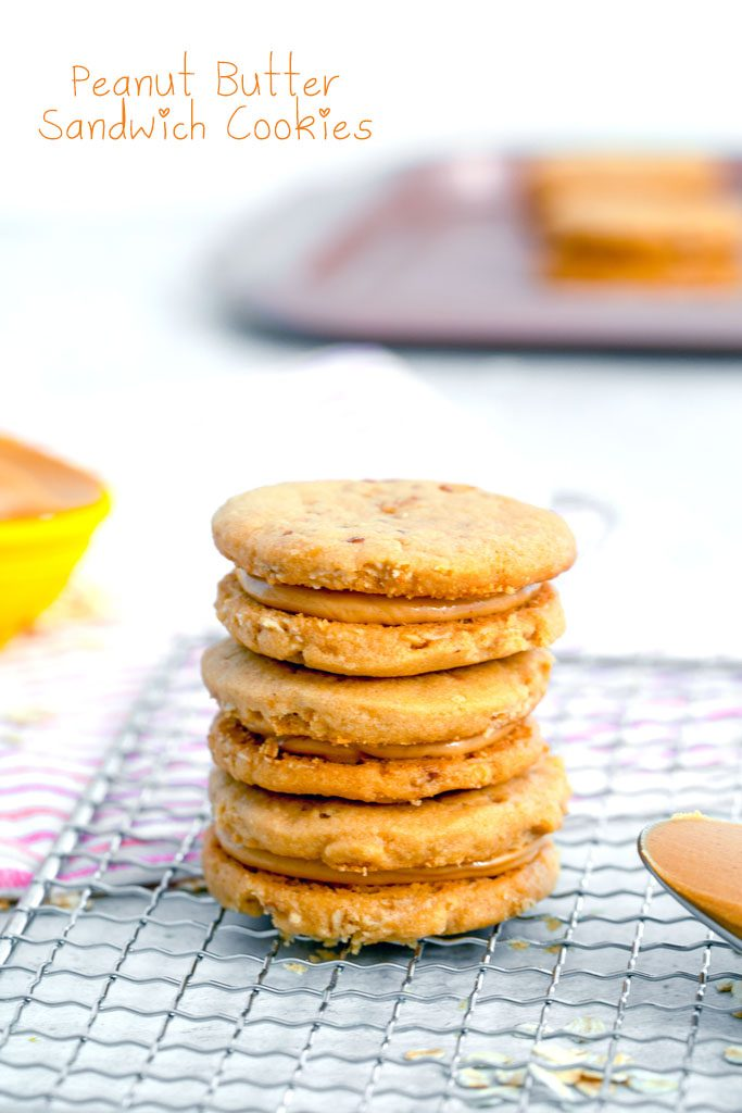 Head-on view of a stack of three peanut butter sandwich cookies on a cooling rack with spoon of peanut butter and cookies in the background with recipe title at top