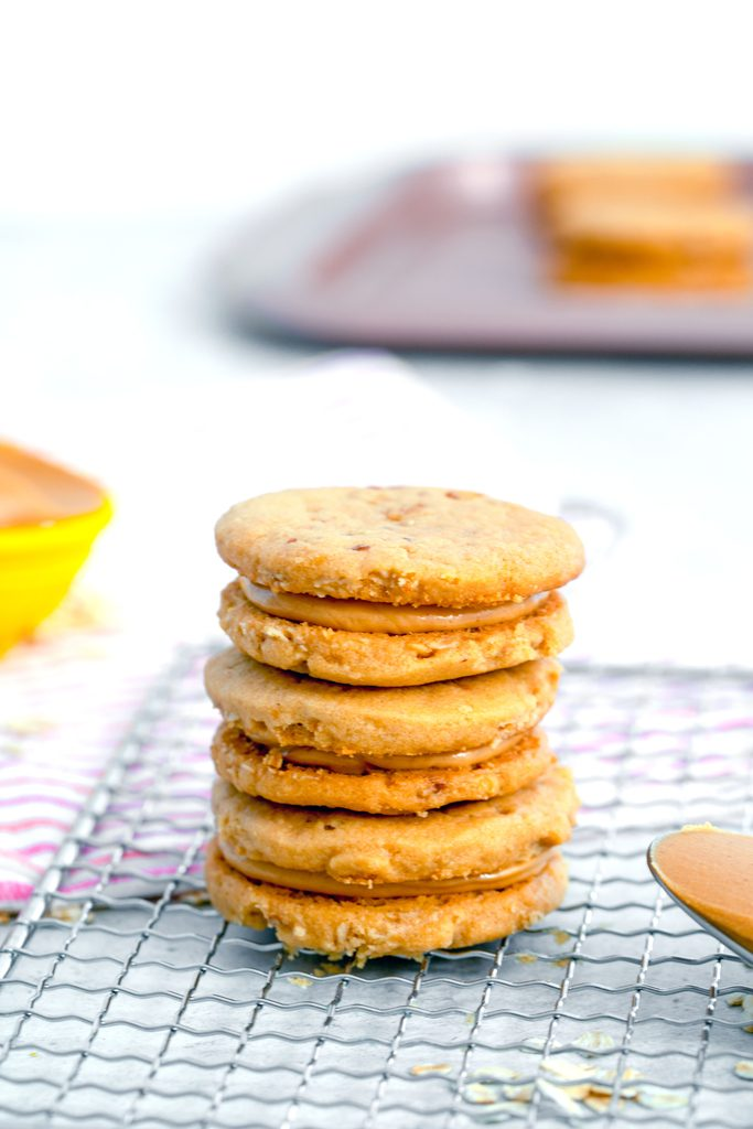 Head-on view of a stack of three peanut butter sandwich cookies on a cooling rack with spoon of peanut butter and cookies in the background