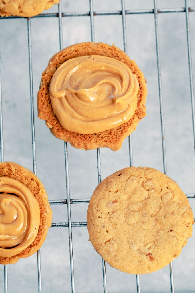 Overhead view of peanut butter cookies on baking rack with some filled with peanut butter cream