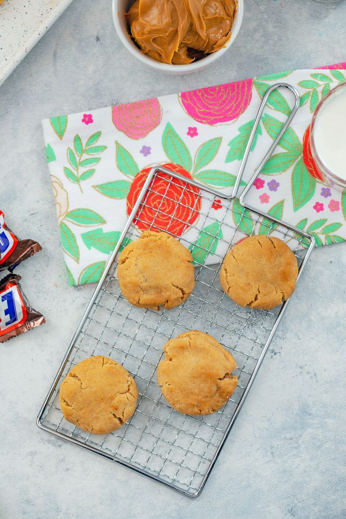 Overhead view of four peanut butter Snickers cookies on a baking rack over a flowered tea towel with mini Snickers bars, bowl of peanut butter, and glass of milk in background