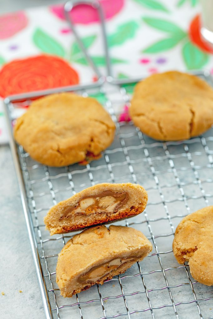 Overhead view of peanut butter Snickers cookies on a baking rack with one cut in half to show Snickers inside with flowered tea towel in the background