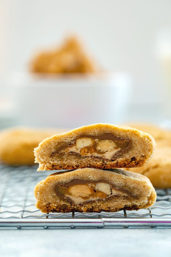 Head-on closeup view of two halves of a peanut butter Snickers cookie stacked on top of each other so you can see the Snickers in the middle