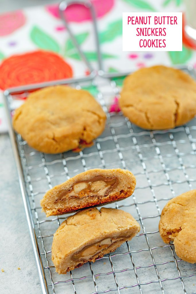 Overhead view of peanut butter Snickers cookies on a baking rack with one cut in half to show Snickers inside with flowered tea towel in the background and recipe title at top