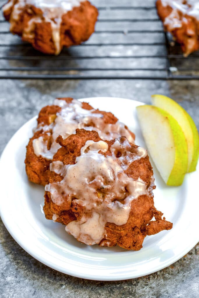 Overhead view of a pear fritter on a white plate with sliced pears and a baking rack with more pear fritters in the background