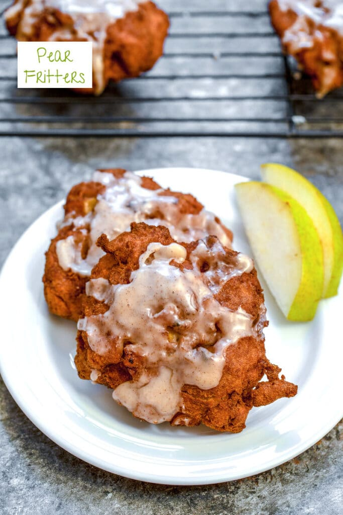 Overhead view of a pear fritter on a white plate with sliced pears, a baking rack with more pear fritters in the background, and recipe title at top