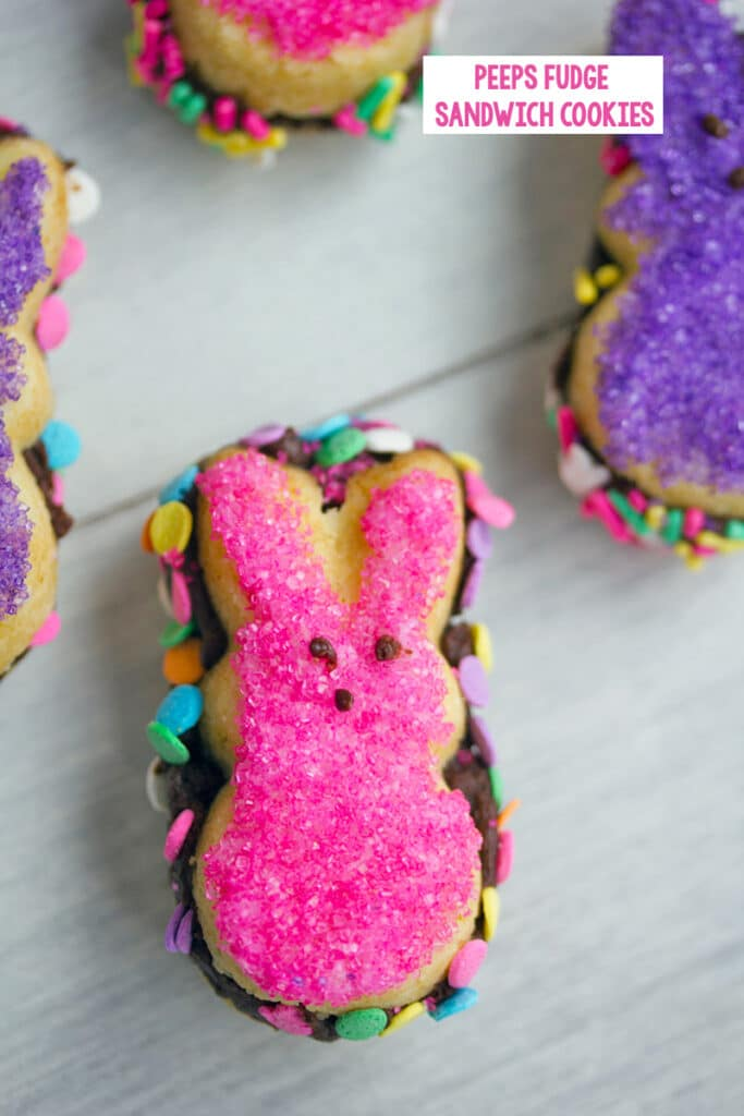 Overhead view of pink Peeps fudge sandwich cookie with more cookies in background and recipe title at top
