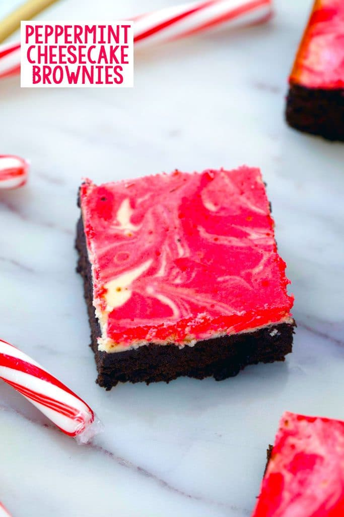 Overhead view of peppermint cheesecake brownie on a marble surface with candy canes in the background and recipe title at the top