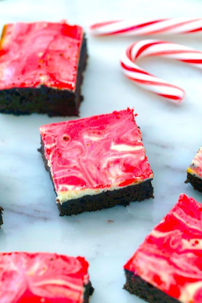 Overhead view of multiple peppermint cheesecake brownies set out on a marble surface with candy canes in the background