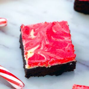 Peppermint Cheesecake Brownies -- These Peppermint Cheesecake Brownies are packed with festive peppermint flavor with a dreamy red and white swirl, making them the perfect holiday party dessert | wearenotmartha.com