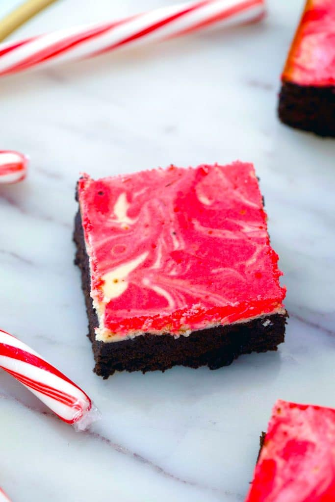 Overhead view of peppermint cheesecake brownie on a marble surface with candy canes in the background