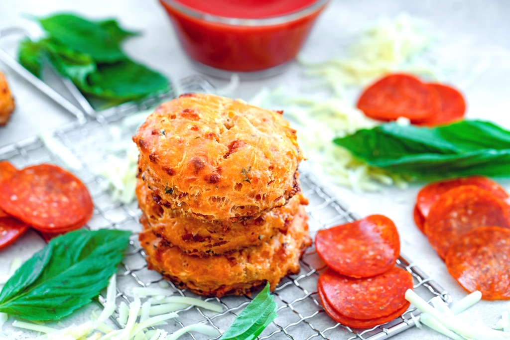 Landscape overhead view of stack of pepperoni pizza biscuits on a small cooling rack with pepperoni, shredded cheddar, and basil with small bowl of pizza sauce in background.