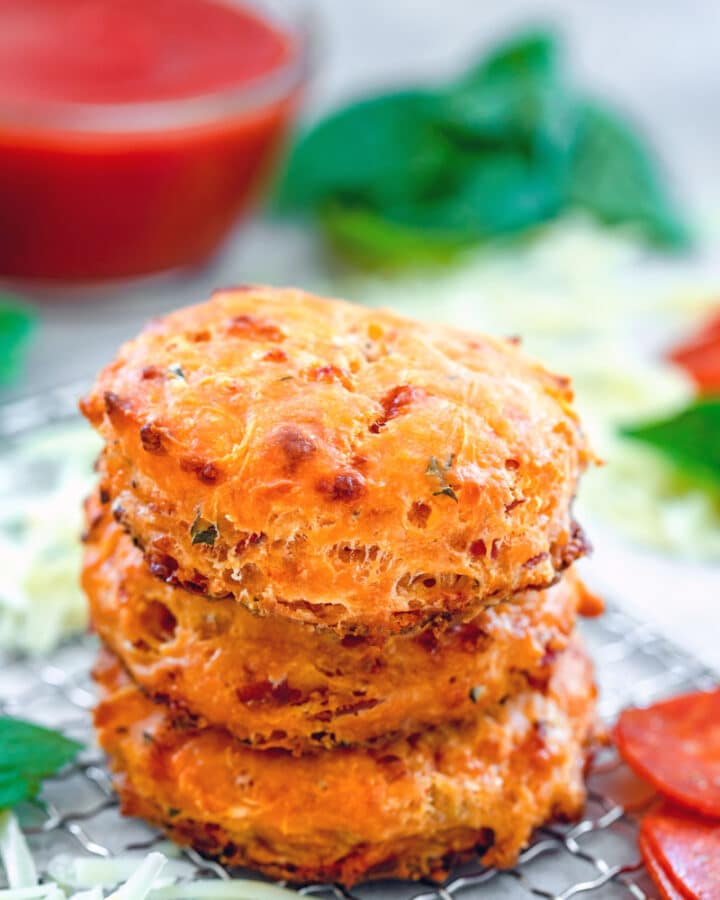 Head-on view of a stack of three pepperoni pizza biscuits surrounded by shredded cheese, basil leaves, pepperoni, and small bowl of tomato sauce