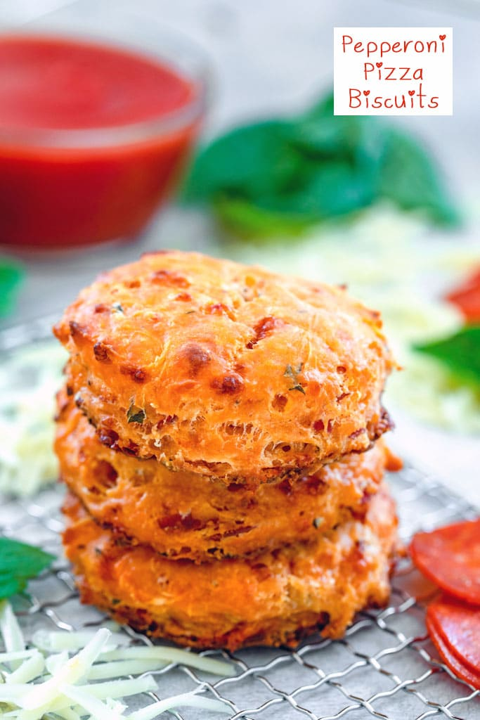 Head-on closeup view of a stack of three pepperoni pizza biscuits on a small baking rack surrounded by pepperoni, shredded cheddar cheese, and basil with small bowl of tomato sauce in background and recipe title at top