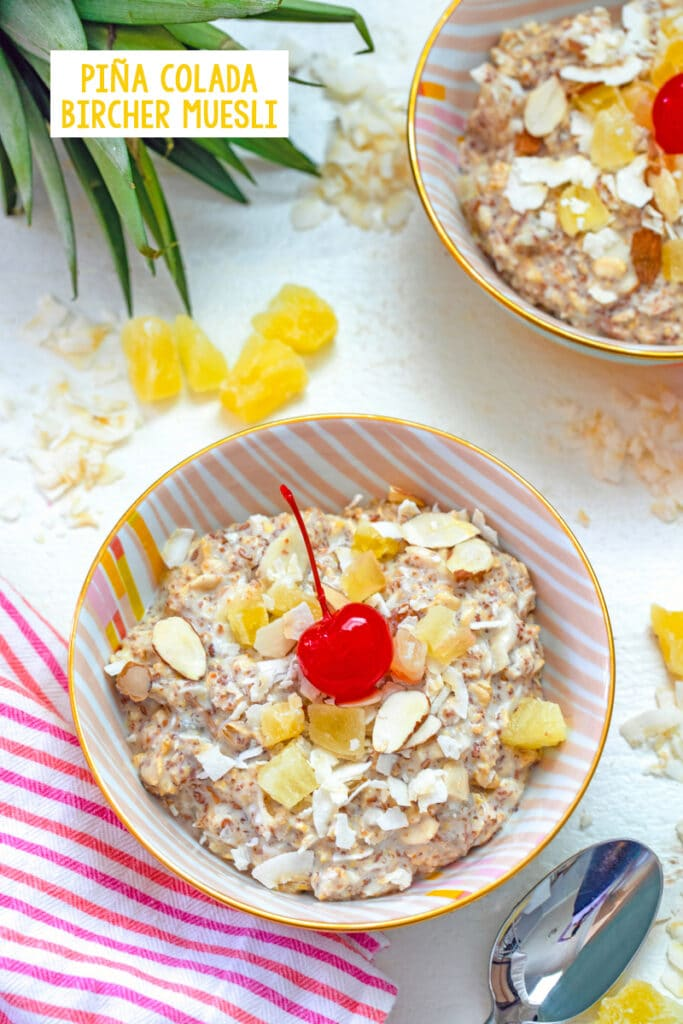 Overhead view of a bowl of piña colada bircher muesli with a cherry on top with second bowl, dried pineapple, and coconut in background and recipe title at top
