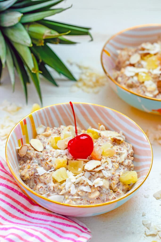 Head-on view of a bowl of piña colada bircher muesli with cherry on top and pineapple in background