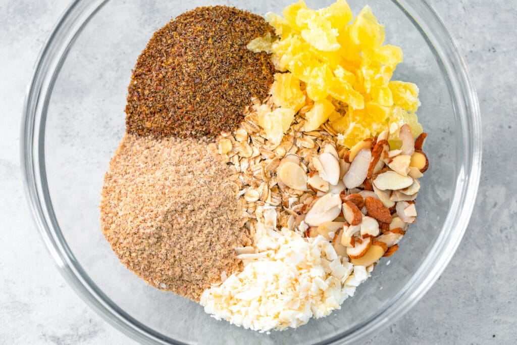 Overhead view of a bowl with oats, wheat germ, ground flaxseed, dried pineapple, sliced almonds, and coconut flakes