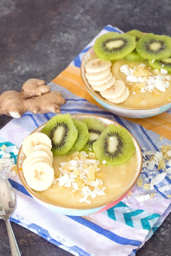 From a distance view of two pineapple banana ginger smoothie bowls with sliced bananas and kiwi and shredded coconut with a spoon, coconut, and ginger in the background