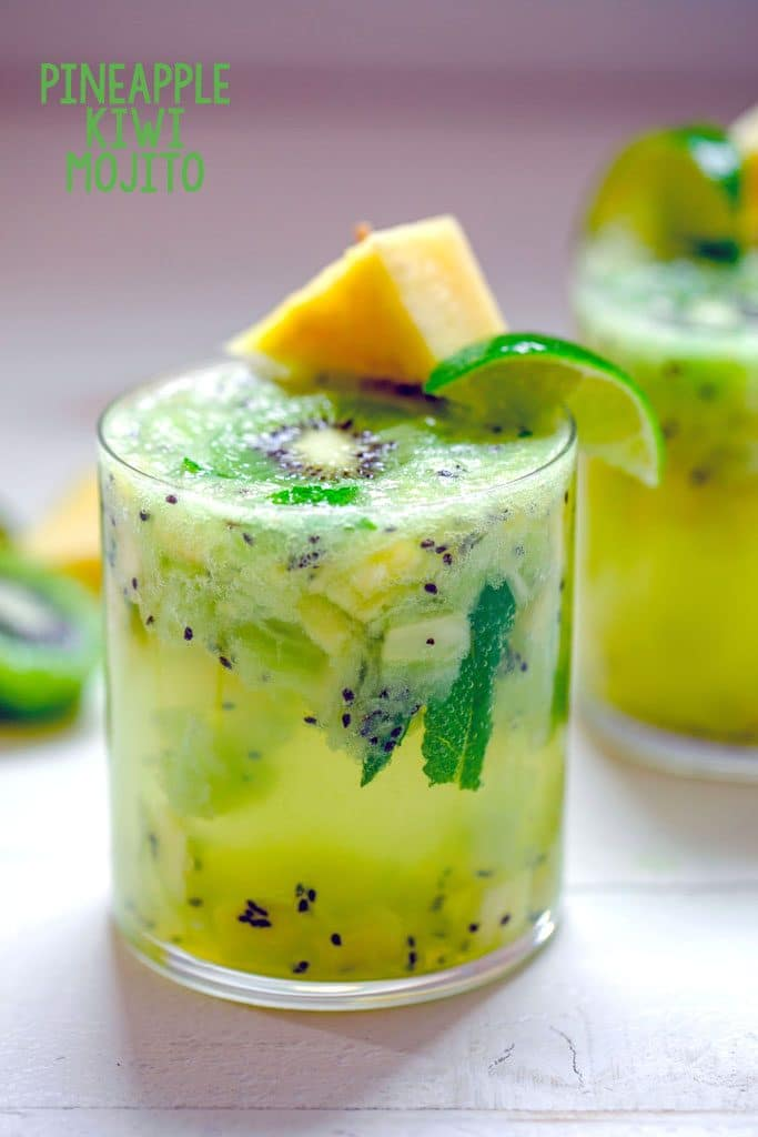 "Head-on image of glass of pineapple kiwi mojito with lots of chopped pineapple and kiwi and pineapple and lime garnish with ""Pineapple Kiwi Mojito"" text at top"