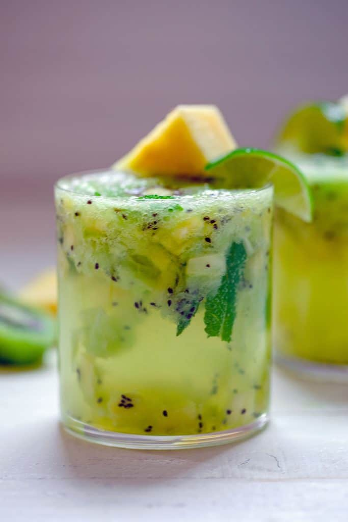 Head-on closeup of pineapple kiwi mojito with lots of chopped pineapple, kiwi, and mint muddled in glass and pineapple and lime garnish