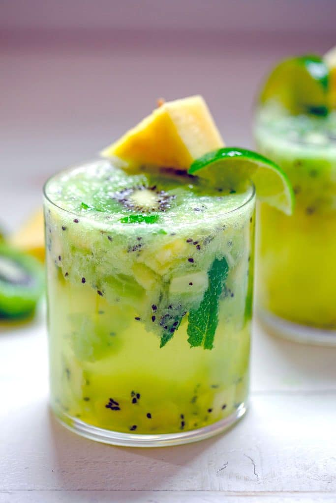 Head-on image of glass of pineapple kiwi mojito with lots of chopped pineapple and kiwi and pineapple and lime garnish