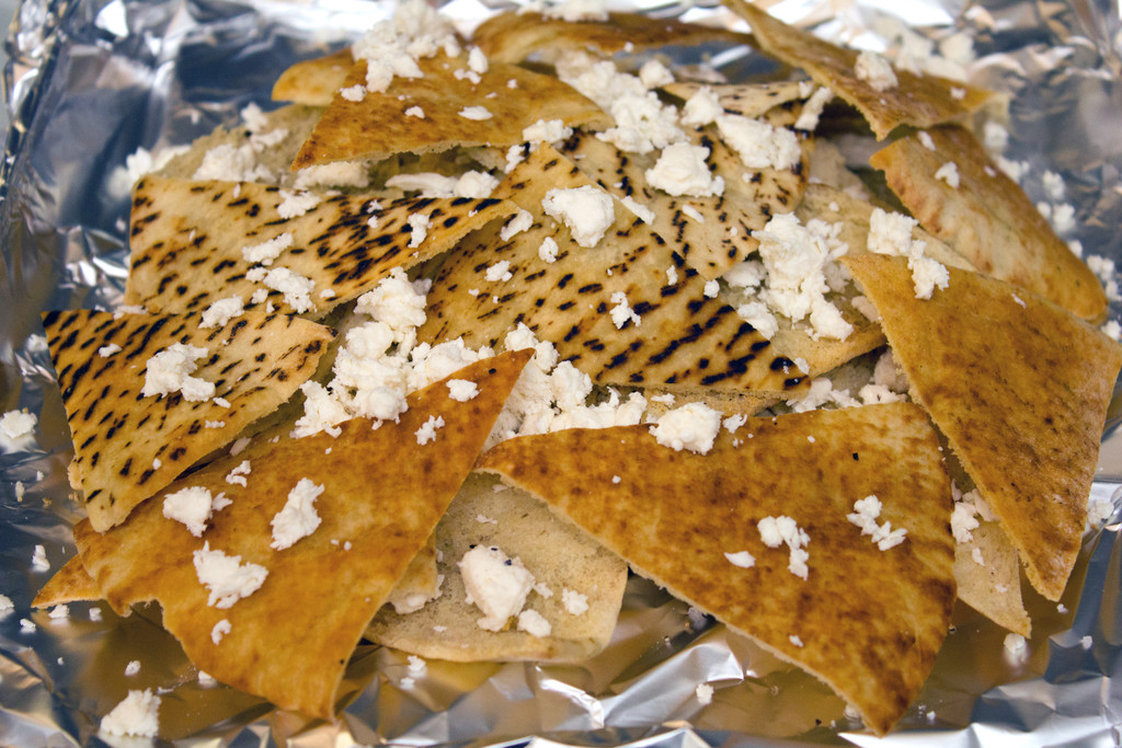 Pita chip triangles piled high on a cookie sheet with crumbled feta