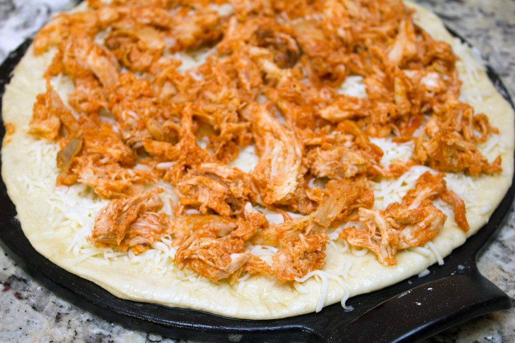 Pizza dough rolled into a round on a pizza pan and covered with mozzarella cheese and shredded buffalo chicken