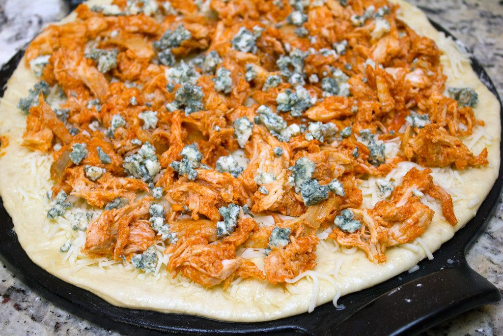 Pizza dough rolled into a round on a pizza pan and covered in mozzarella cheese, shredded buffalo chicken, and crumbled blue cheese