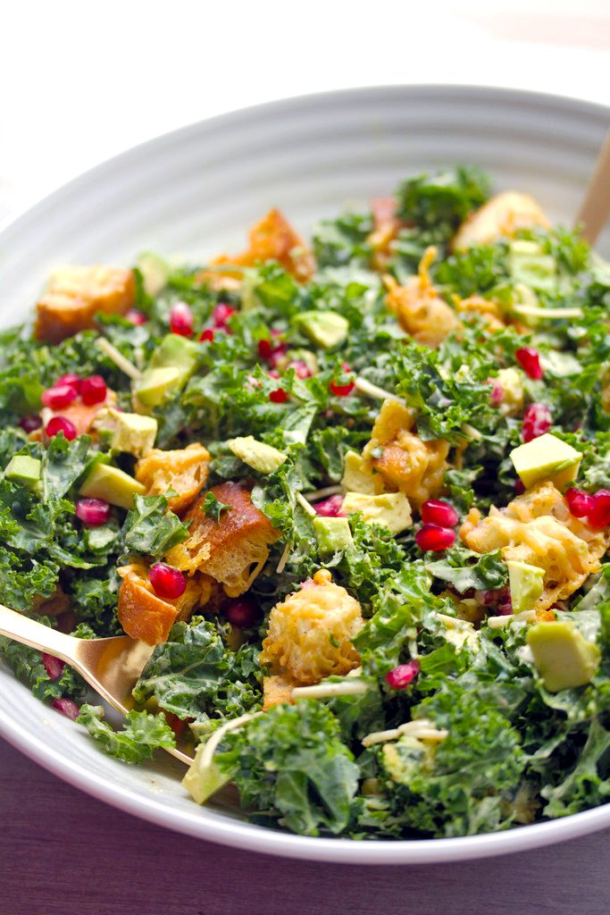 Overhead view of pomegranate avocado kale salad with parmesan croutons in a big serving bowl