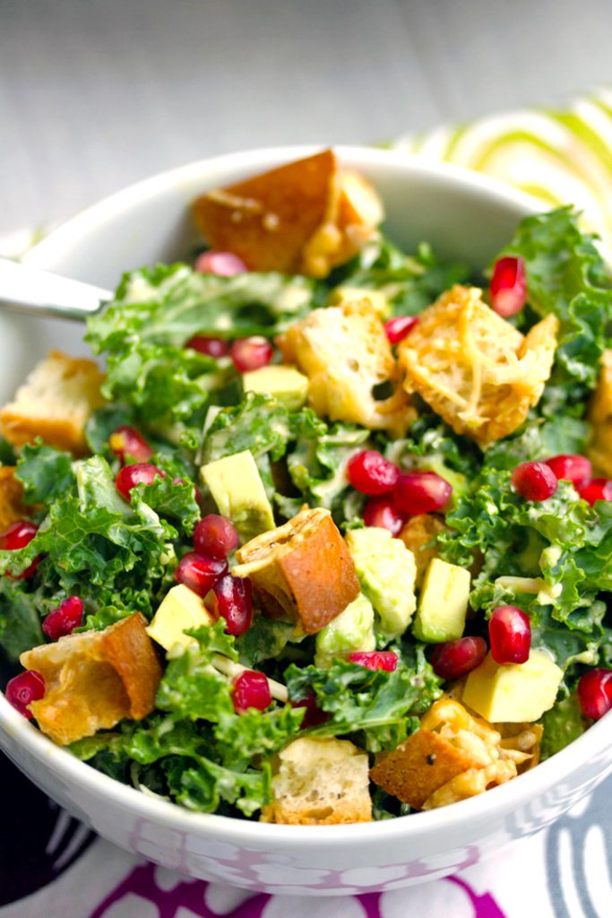 Overhead closeup view of pomegranate avocado kale salad with parmesan croutons in a white bowl