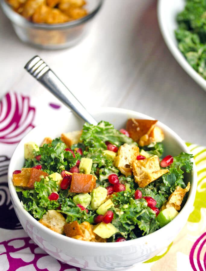 Pomegranate Avocado Kale Caesar Salad -- Caesar salads are nice, but they're even better when made with kale and avocado. This Pomegranate Avocado Kale Caesar Salad with parmesan croutons is the most delicious side or entree salad! | wearenotmartha.com