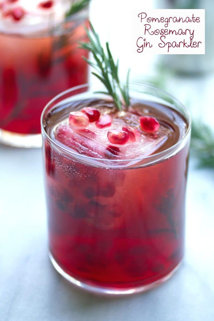 Head-on close-up view of pomegranate and gin cocktail with rosemary with pomegranate and rosemary garnish, second cocktail in the background, and recipe title at top