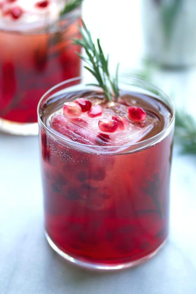 Head-on close-up view of pomegranate and gin cocktail with rosemary with pomegranate and rosemary garnish and second cocktail in the background