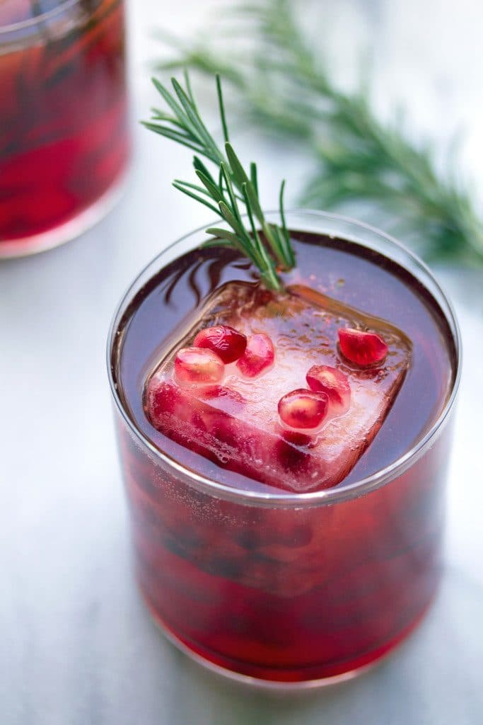 Overhead close-up of a pomegranate and gin cocktail with rosemary garnish and large ice cube floating with pomegranate arils and rosemary sprig in the background