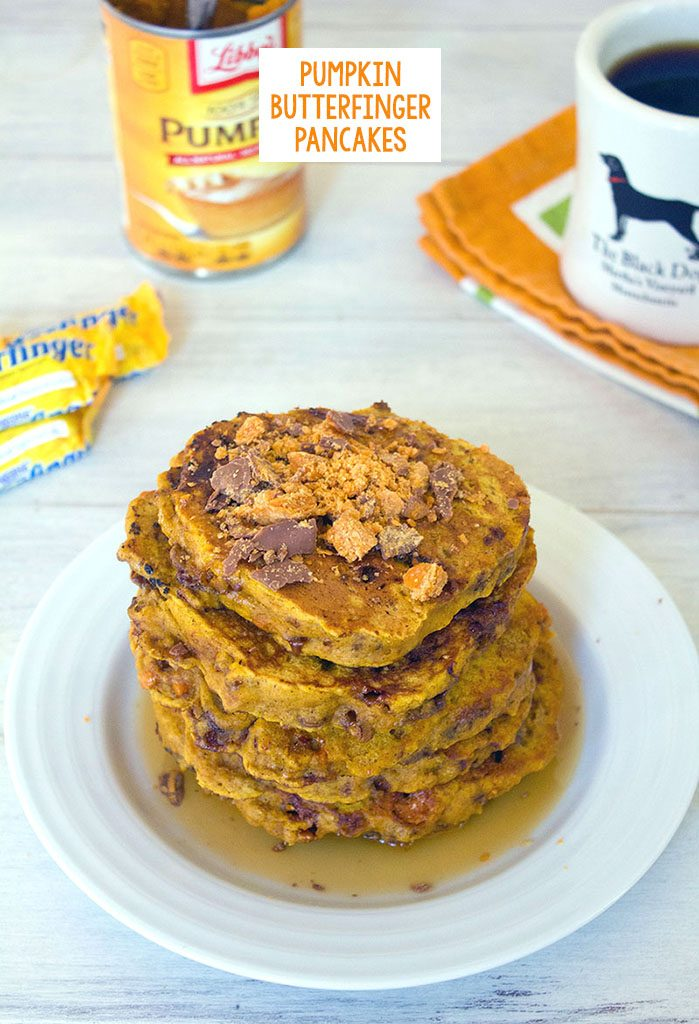 Head-on view of a stack of pumpkin butterfinger pancakes with crushed Butterfingers on top, coffee, candy, and a can of pumpkin in the background and recipe title at top