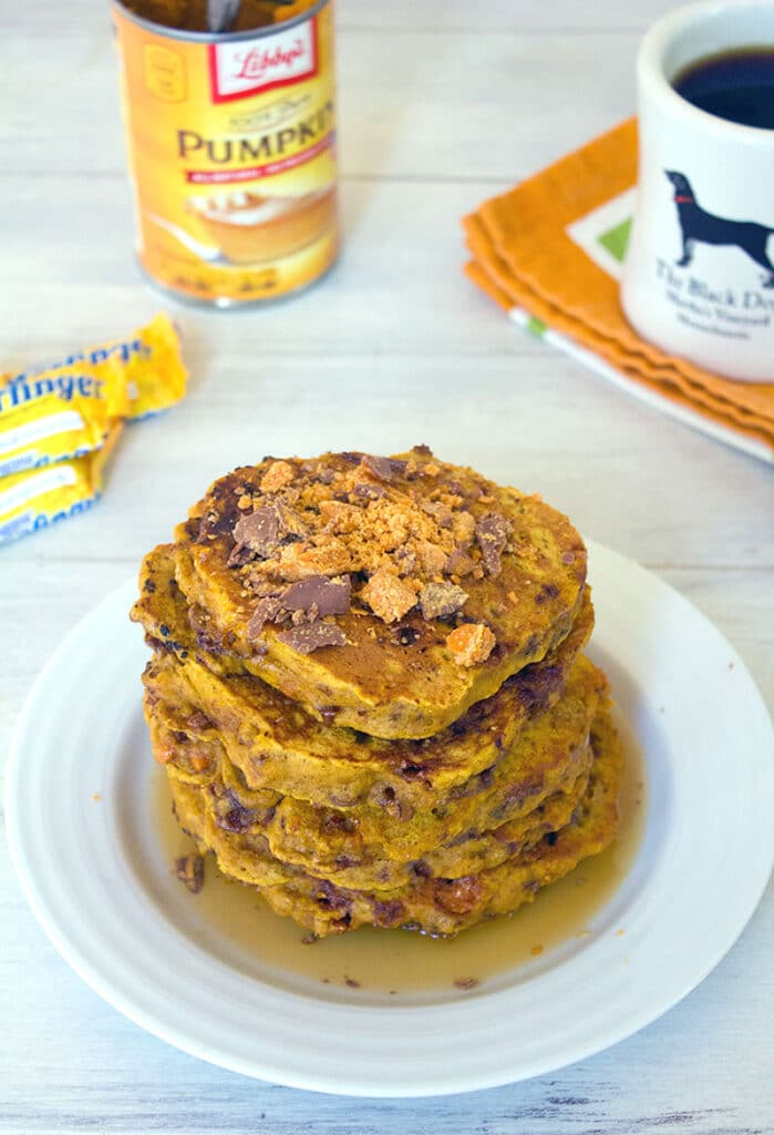 Head-on view of a stack of pumpkin butterfinger pancakes with crushed Butterfingers on top, coffee, candy, and a can of pumpkin in the background