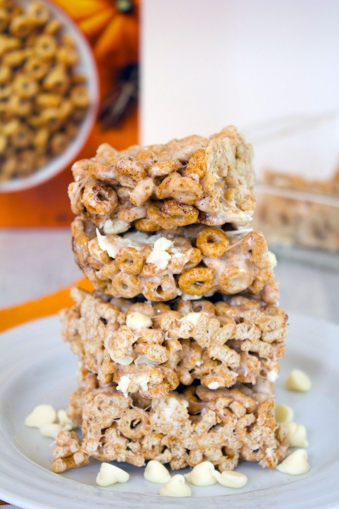 Head-on close-up view of four pumpkin Cheerios marshmallow treats on a white plate surrounded by white chocolate chips