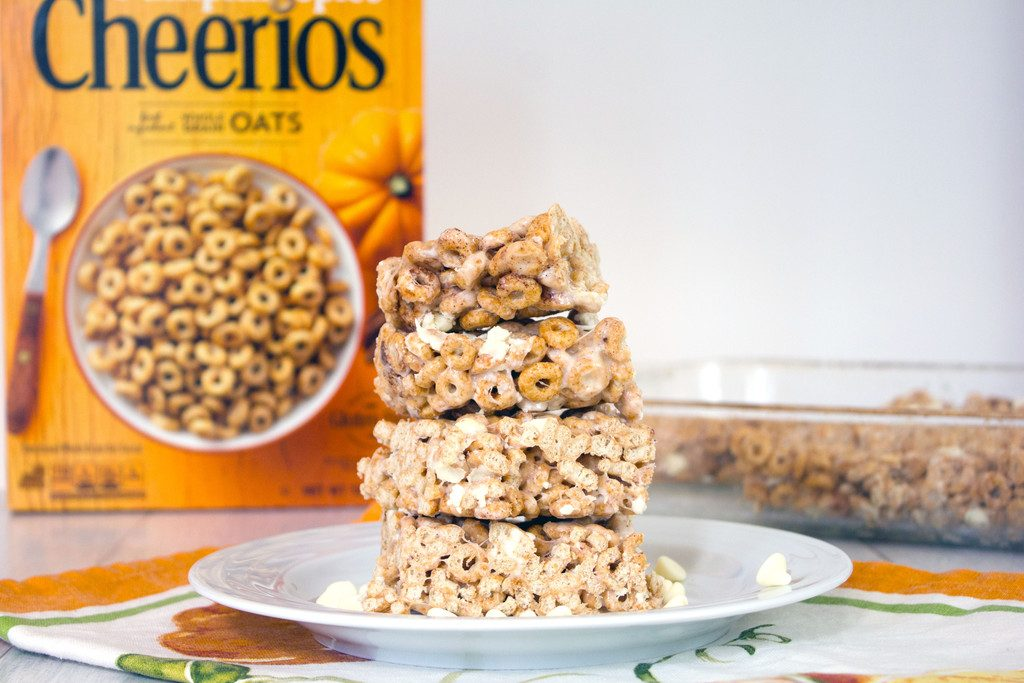 Landscape head-on view of a stack of four pumpkin Cheerios marshmallow treats on a white plate with white chocolate chips with box of cereal and more bars in pan in the background