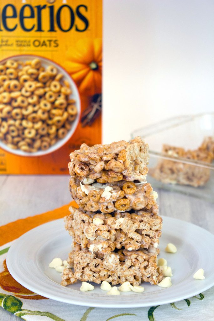 Head-on view of a stack of four pumpkin Cheerios marshmallow treats on a white plate surrounded by white chocolate chips with box of cereal and pan of bars in the background