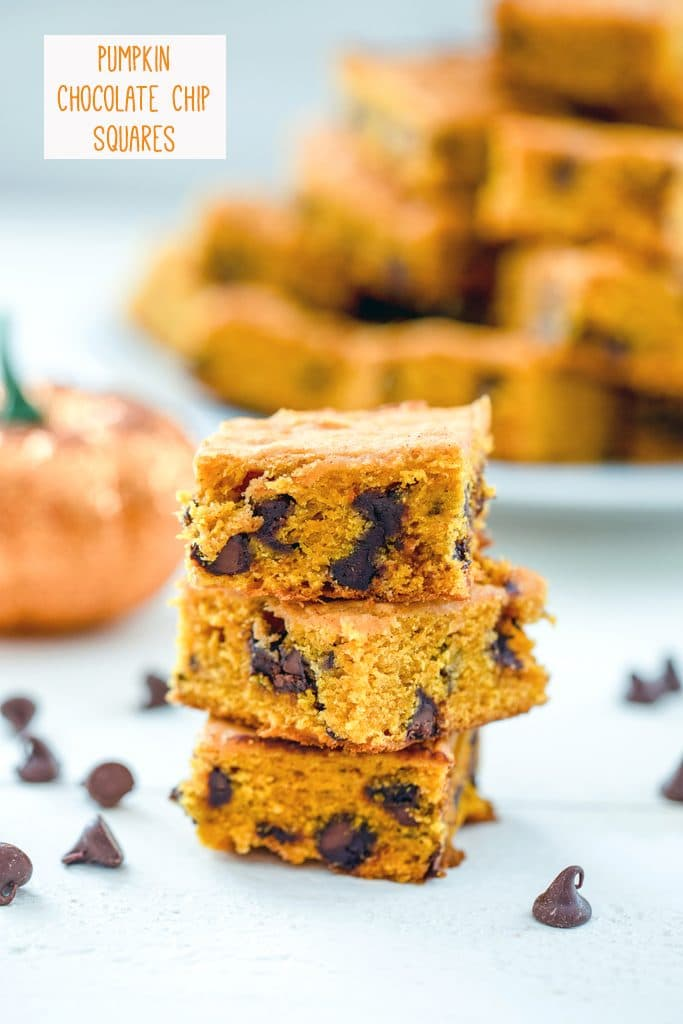 """Head-on view of a stack of three pumpkin chocolate chip bars with chocolate chops scattered around and a glitter pumpkin and platter full of more bars in the background with """"Pumpkin Chocolate Chips Squares"""" text at top"""