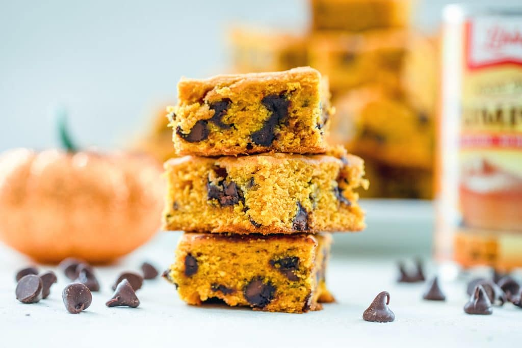 A landscape view of three pumpkin chocolate chip squares with chocolate chips scattered around, and a glitter pumpkin, can of pumpkin pie puree, and plate full of more bars in the background
