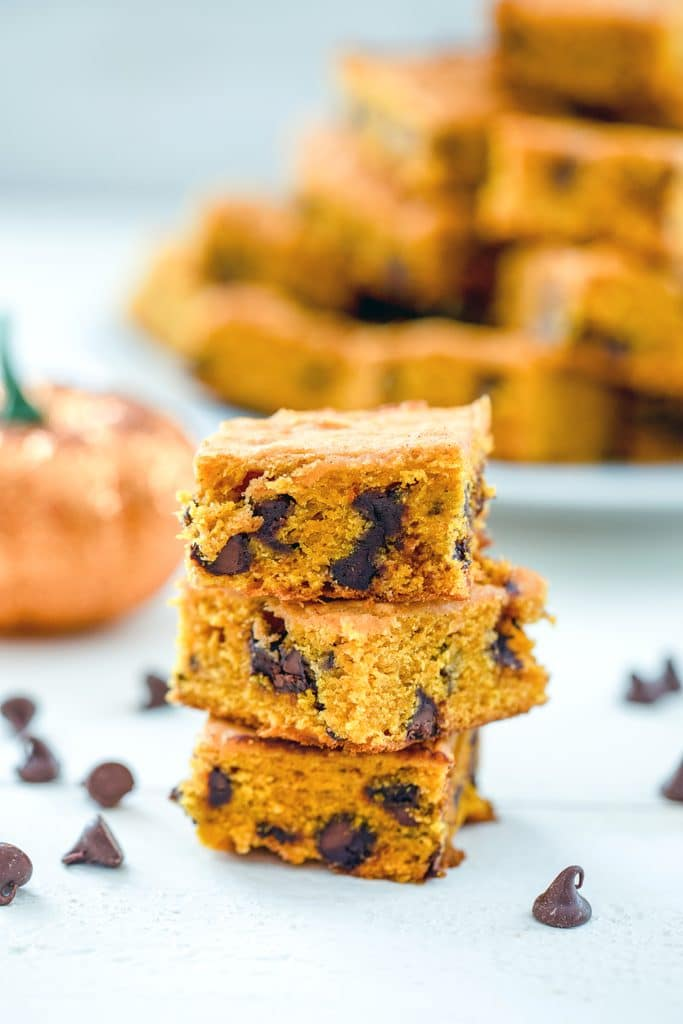 Head-on view of a stack of three pumpkin chocolate chip bars with chocolate chops scattered around and a glitter pumpkin and platter full of more bars in the background