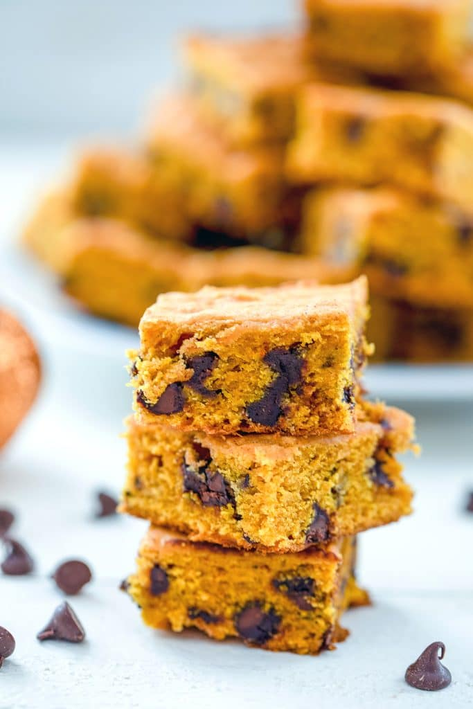 A head-on view of three pumpkin chocolate chip squares with chocolate chips scattered around and a platter full of more bars in the background