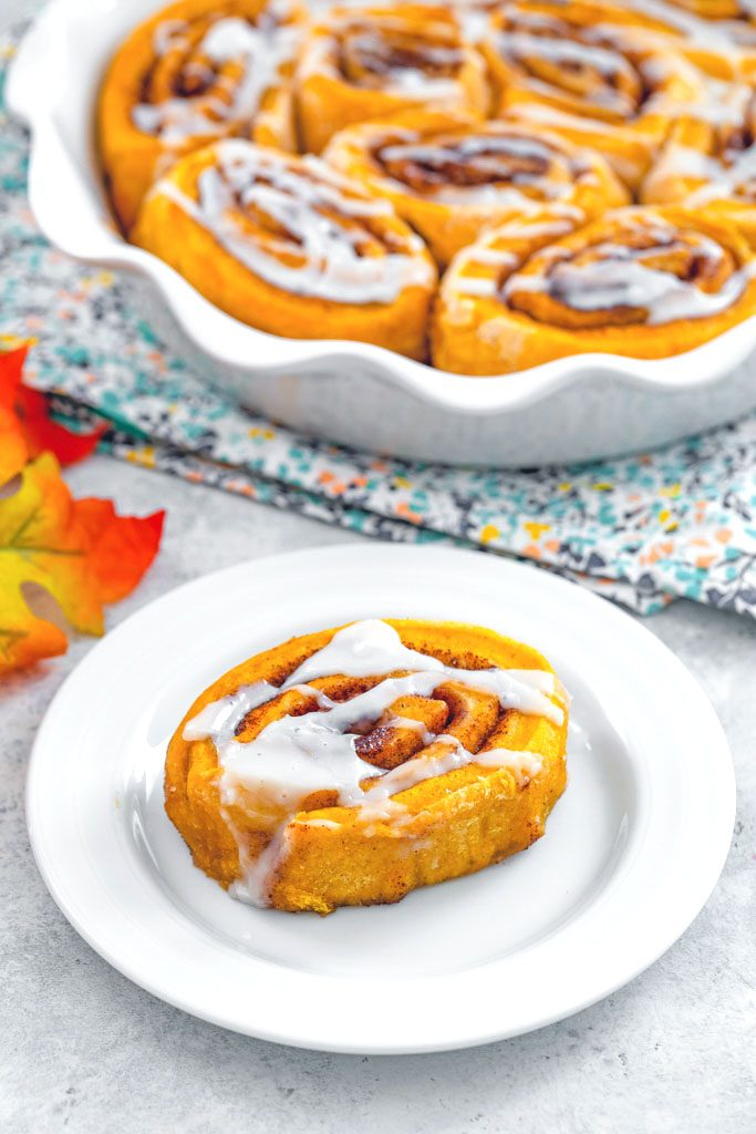 Overhead view of a pumpkin cinnamon roll with icing on a white plate with pie plate of cinnamon rolls and fall leaves in background