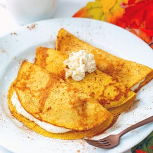 Head-on view of a plate with three pumpkin crepes filled and topped with maple cream cheese with fall leaves all around