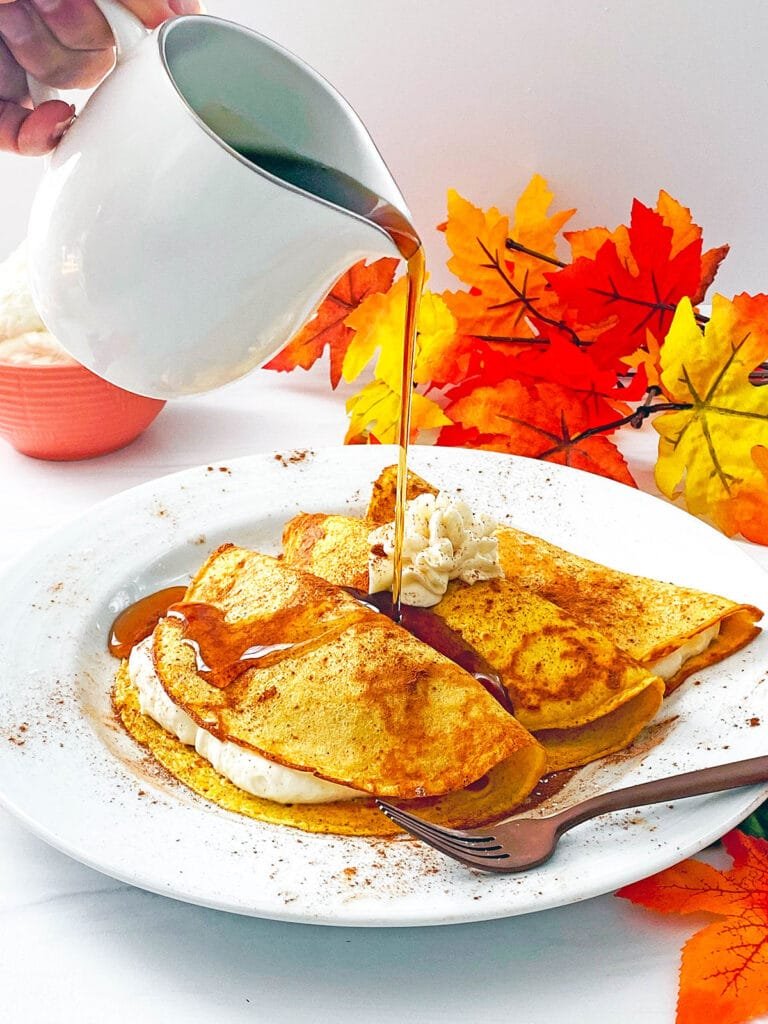 Pitcher of maple syrup being poured over plate of pumpkin crepes with maple cream cheese filling with fall leaves all around