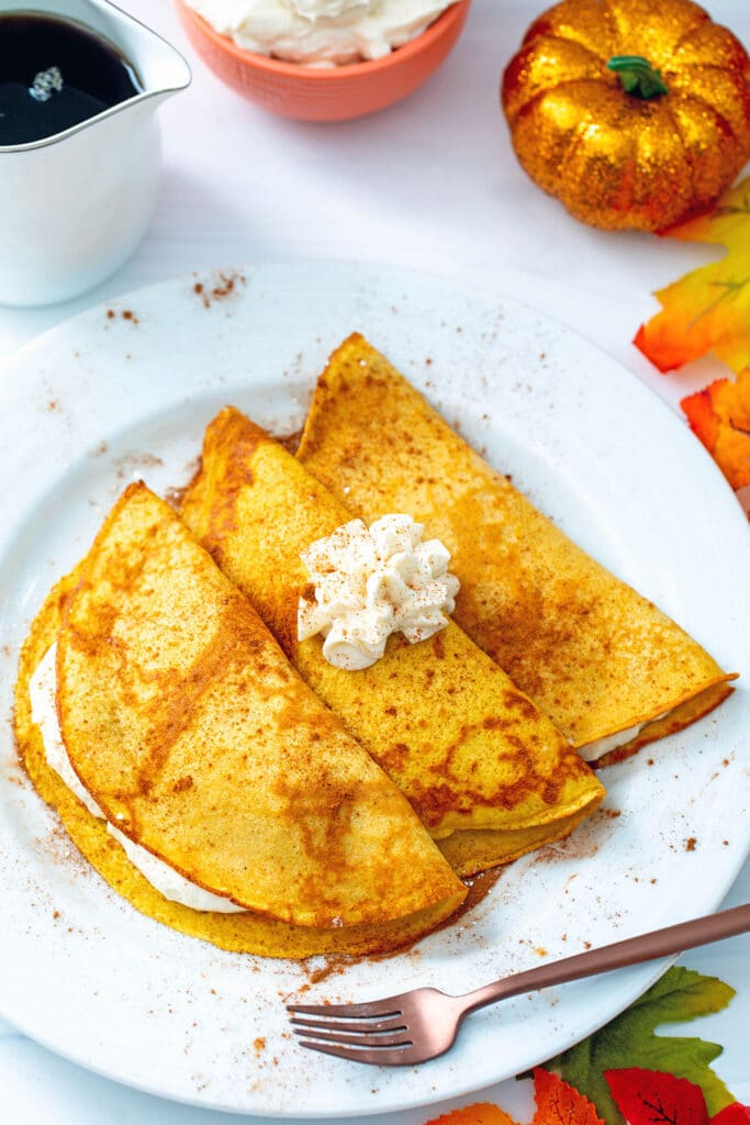 Three pumpkin crepes on a plate filled and topped with maple cream cheese filling with a rose fold fork, pitcher of syrup, and fall leaves and a pumpkin in background